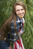 Teenage girl with blue plaid shirt holding American flag scarf. Stock Photography