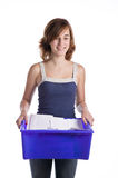 Teenage girl with a blue recycling basket Stock Images
