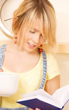 Teenage girl with book and mug Stock Images