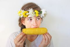A teenage girl with a bouquet on her head eats corn. A cute teenage girl with a bouquet of flowers on her head eats yellow corn on the cob Stock Photo