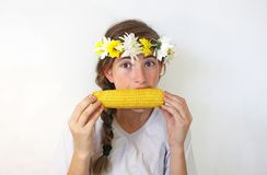 A teenage girl with a bouquet on her head eats corn. A cute teenage girl with a bouquet of flowers on her head eats yellow corn on the cob Royalty Free Stock Photography