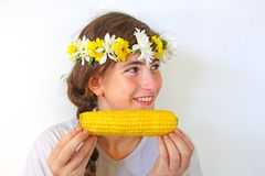 A teenage girl with a bouquet on her head eats corn. A cute teenage girl with a bouquet of flowers on her head eats yellow corn on the cob Stock Images
