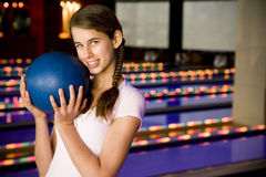 Teenage girl in a bowling alley, holding a blue bowling ball royalty free stock photo