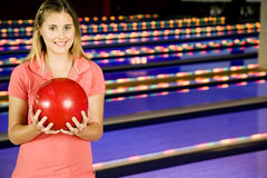 Teenage girl in bowling alley holding a red bowling ball stock photography