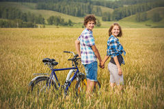 Teenage girl and boy on a bicycle in a summer field of rye Stock Image