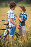 Teenage girl and boy on a bicycle in a summer field of rye Stock Images