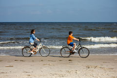 Teenage girl and boy biking on beach Stock Photos