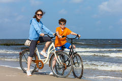 Teenage girl and boy biking on beach Royalty Free Stock Photo