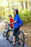 Teenage girl and boy biking on forest trails Royalty Free Stock Photography