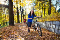 Teenage girl and boy biking on forest trails Royalty Free Stock Images