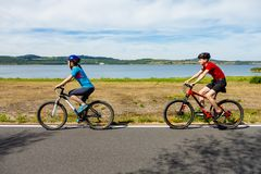 Teenage girl and boy cycling stock image
