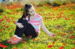 Teenage girl with braces in a field of wild red flowers Stock Photo