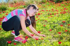 Teenage girl with braces in a field of wild red flowers Stock Image