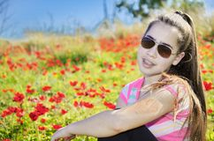 Teenage girl with braces in a field of wild red flowers Royalty Free Stock Photos