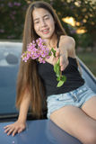 Teenage girl with braces and long hair sitting on car Stock Photo