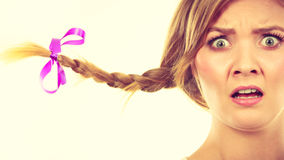 Teenage girl in braid hair making shocked face. Emotions expressions, fooling around concept. Astonished teenage girl in blonde braid windblown hair making funny Stock Photo