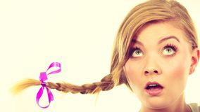 Teenage girl in braid hair making shocked face. Emotions expressions, fooling around concept. Astonished teenage girl in blonde braid windblown hair making funny Royalty Free Stock Image