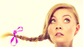 Teenage girl in braid hair making thinking face. Reflections expression, having idea concept. Teenage girl in blonde braid windblown hair making thinking face Stock Photo