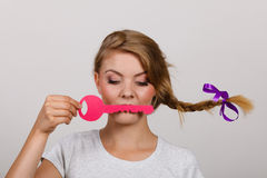 Teenage girl with braid holding key on lips. Language barrier concept. Teenage blonde girl with braid hair holding pink key on lips Stock Photos