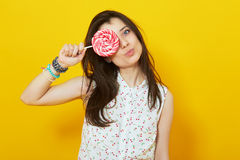 Teenage girl on bright vivid yellow background holding lollipop stock photo