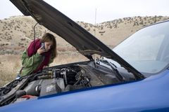 Teenage girl with a broken car Stock Images