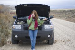 Teenage girl with a broken car Stock Photos