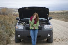 Teenage girl with a broken car Royalty Free Stock Photos