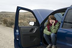 Teenage girl with a broken car Stock Photography