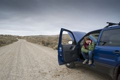 Teenage girl with a broken car Stock Image