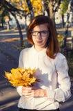 Teenage girl with bundle of maple leaves Stock Photo