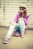 Teenage girl in cap and sunglasses sits on skateboard Stock Photo