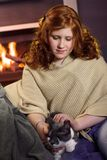 Teenage girl caress cat at home fireplace Royalty Free Stock Image