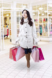 Teenage girl carries shopping bags at mall. Picture of pretty teenage girl walking at mall while wearing winter coat and carrying shopping bags Stock Image