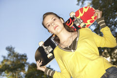 A teenage girl carrying a skateboard. Royalty Free Stock Images