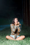 Teenage girl caucasian blowing glitter from her hands sitting Stock Images