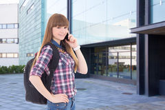Teenage girl with cell phone standing on street against school b Stock Photos