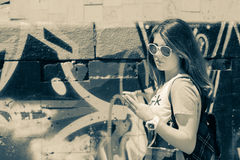 Teenage girl  with cellphone near graffiti wall. Sepia effect Stock Image