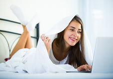 Teenage girl chatting online covered with blanket Royalty Free Stock Images