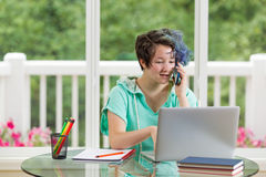 Teenage girl chatting on phone while working on her studies at h Royalty Free Stock Image