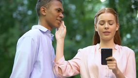 Teenage girl chatting smartphone rejecting mixed-race boyfriend kiss, addiction. Stock footage stock video