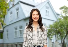 Teenage girl in checkered shirt over house stock photography