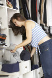Teenage Girl Choosing Clothes From Wardrobe In Bedroom Stock Image