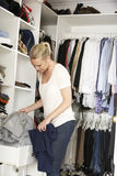 Teenage Girl Choosing Clothes From Wardrobe In Bedroom stock photography