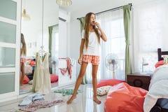 Teenage girl choosing clothing in closet. 10 years old pre teen girl choosing outfit in her closet. Messy in the bedroom, clothing on the floor. Teenager is stock image