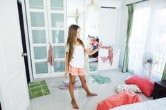 Teenage girl choosing clothing in closet. 10 years old pre teen girl choosing outfit in her closet. Messy in the bedroom, clothing on the floor. Teenager is stock photos