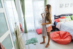 Teenage girl choosing clothing in closet. 10 years old pre teen girl choosing outfit in her closet. Messy in the bedroom, clothing on the floor. Teenager is royalty free stock photography