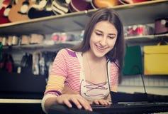 Teenage girl choosing synthesizer Royalty Free Stock Image