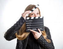 Teenage girl with clapperboard. Teenage girl in black clothes, blonde with long hair is holding clapperboard, on white background Royalty Free Stock Images