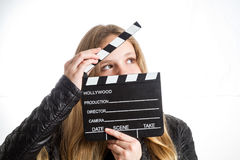 Teenage girl with clapperboard. Teenage girl in black clothes, blonde with long hair is holding clapperboard, on white background Royalty Free Stock Photos