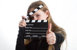 Teenage girl with clapperboard. Teenage girl in black clothes, blonde with long hair is holding clapperboard, on white background Stock Photos